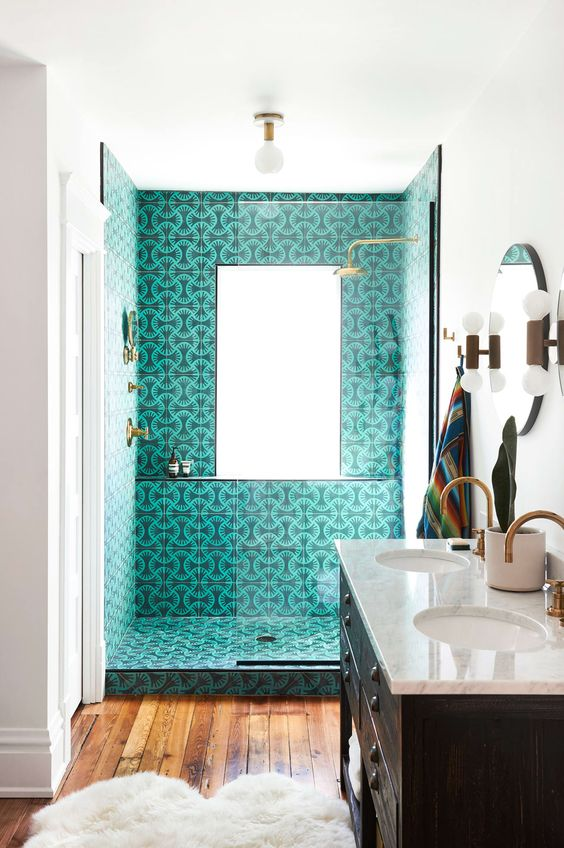 a catchy bathroom in white, with very cool printed turquoise tiles in the shower, a wooden floor and a dark vanity