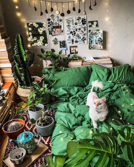 a catchy bedroom with neutral walls, stacks of books, a gallery wall and bright green bedding plus lots of cacti