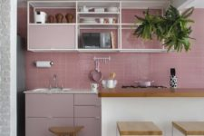 a catchy kitchen with a pink tile backsplash and pale pink cabinets, open shelving and a large white kitchen island