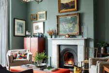 a catchy vintage-inspired living room with grey green walls, creamy and red furniture and a lovely gallery wall