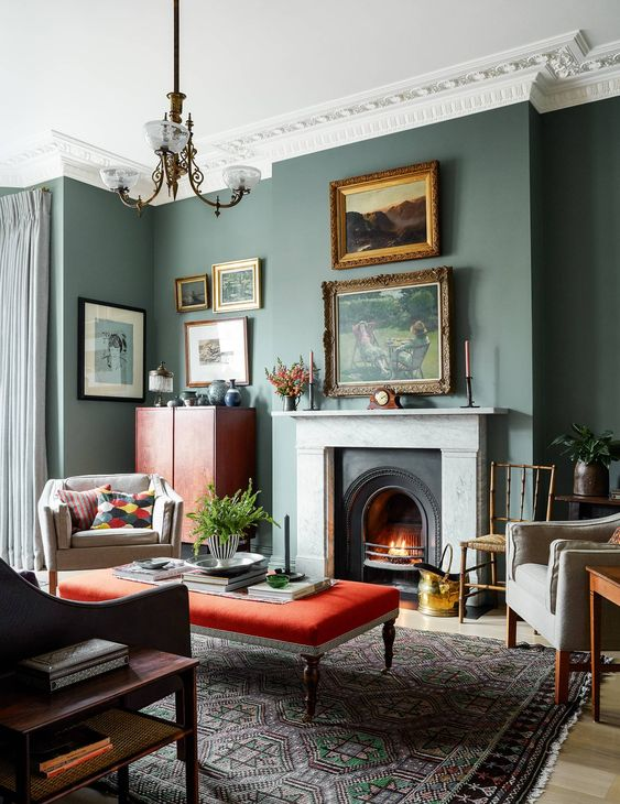 a catchy vintage inspired living room with grey green walls, creamy and red furniture and a lovely gallery wall