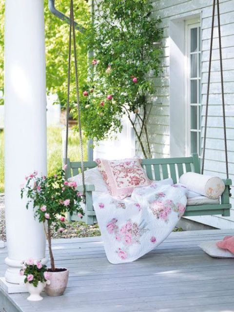 a charming vintage summer porch with a mint hanging daybed with floral bedding, a rose in a pot and more flowers around