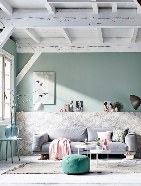 a chic Scandinavian living room with light green walls, a green ottoman and stool, some comfy furniture and a whitewashed ceiling