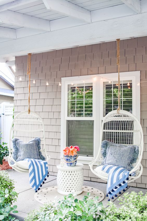 a chic and cozy summer porch with white hanging chairs, a white table, blue printed textiles and some blooms