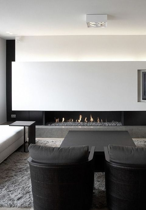 a chic contrasting living room with a white lit up wall with a fireplace, a white sofa, a black table and chairs is wow