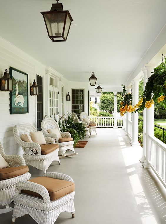 a chic farmhouse neutral porch with white wicker furniture, taupe upholstery, potted greenery and blooms