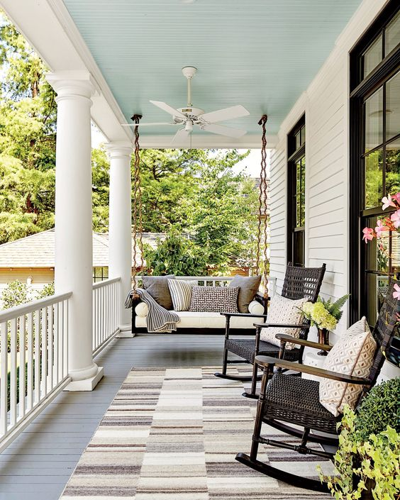 a chic farmhouse porch with a hanging daybed, a couple of rockers and neutral textiles