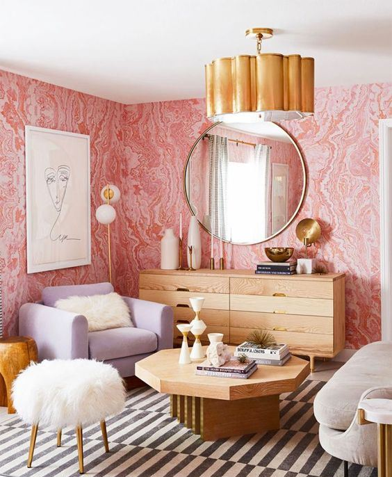 a chic living room with pink printed wallpaper, wooden furniture, a lavender chair, neutral items and touches of gold