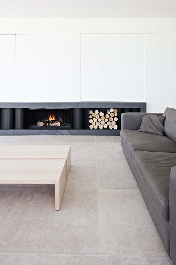a chic minimalist living room with a built-in fireplace and firewood storage, a grey sofa and neutral tables