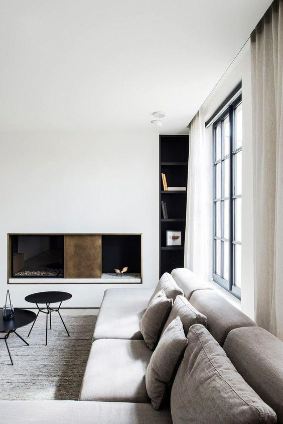 a chic minimalist living room with a white wall with a fireplace, a grey sectional, black furniture and a glazed wall