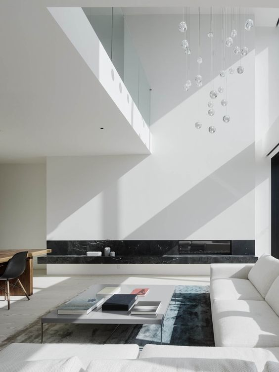 a chic minimalist living space with a glazed wall, bubble chandelier, a white sectional, a built-in fireplace with black marble