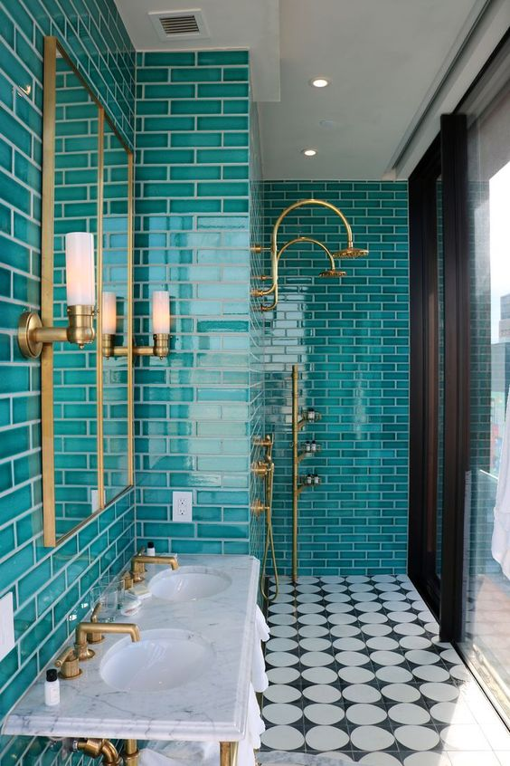 a chic modern bathroom with turquoise tiles, a white free-standing sink, mirrors and touches of gold
