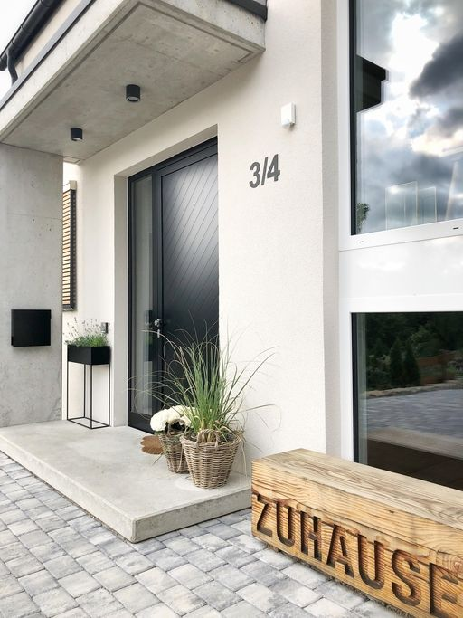 a chic modern entrance with a blakc box planter with blooms, baskets with greenery and blooms and a cool artwork of wood