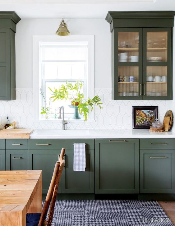 a chic modern farmhouse kitchen in dark green, with a catchy white tile backsplash and touches of brass