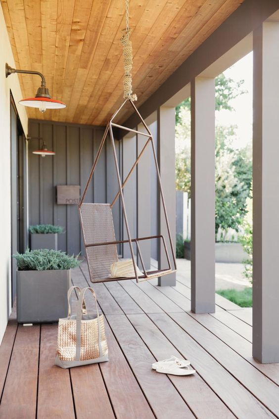 a chic modern porch clad with wood, with pillars, grey metal planters with greenery and a metal suspended chair