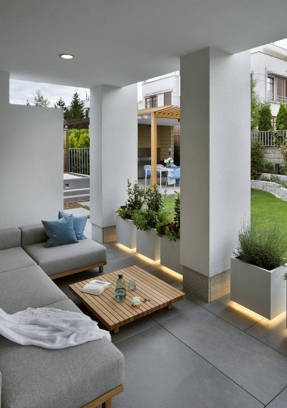 a chic modern porch in grey, with a sectional sofa, floating planters and built in lights