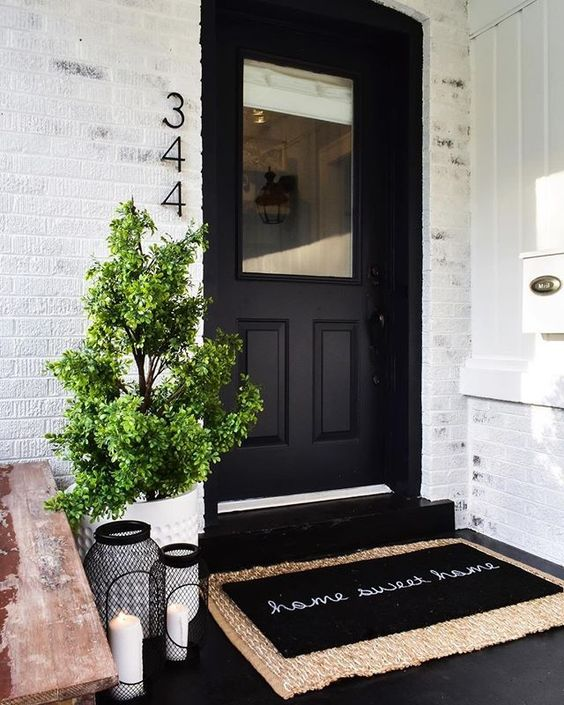 a chic modern porch with a black door, layered rugs, a wooden bench, candle lanterns and a white planter with greenery