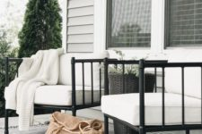 a chic modern porch with white soft chairs, a black tall planter with greenery, a monochromatic rug with fringe is welcoming