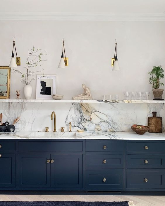 a chic navy kitchen with only lower cabinets, a marble countertop and backsplash, sconces and an open shelf