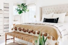 a chic neutral bedroom with a gorgeous creamy bed, a woven bench, some printed textiles and boho hangings on the wall
