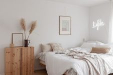 a chic neutral bedroom with a large bed, a wooden cabinet, a neon light and an artwork plus some textiles
