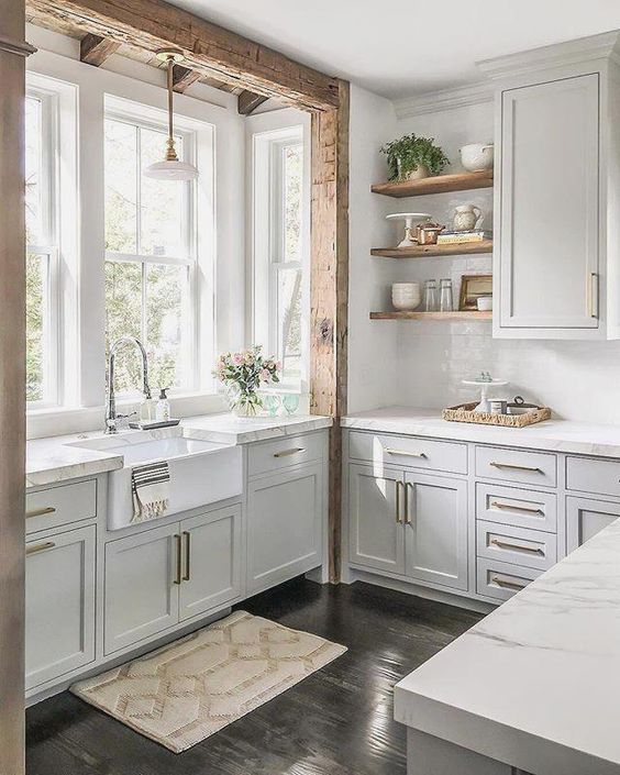 a chic neutral farmhouse kitchen with traditional cabinets, brass handles, wooden shelves and a wooden beam over the sink