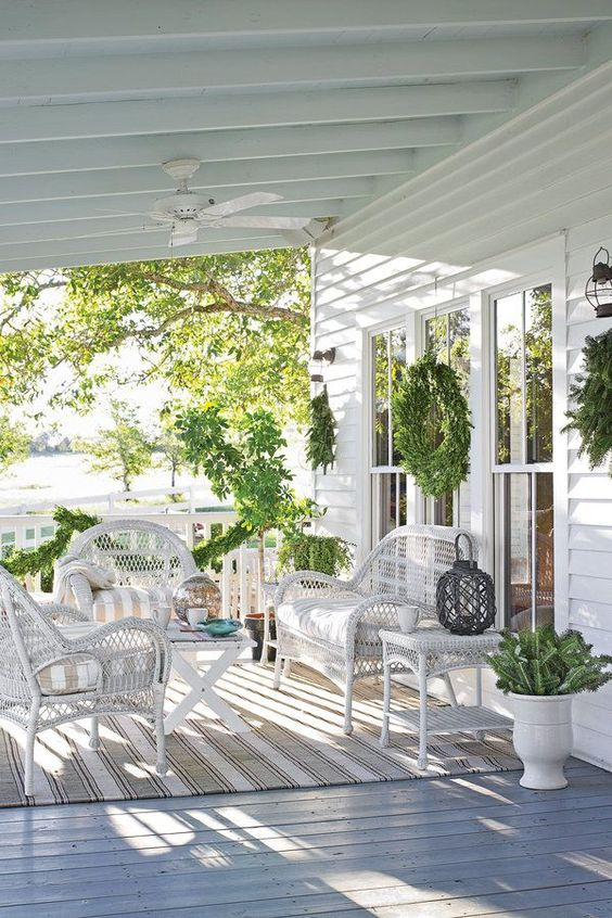 a chic neutral farmhouse porch with striped textiles, white wicker furniture, greenery and candle lanterns