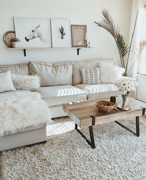 a chic neutral living room with a sectional, a wooden coffee table, a gallery wall on a ledge