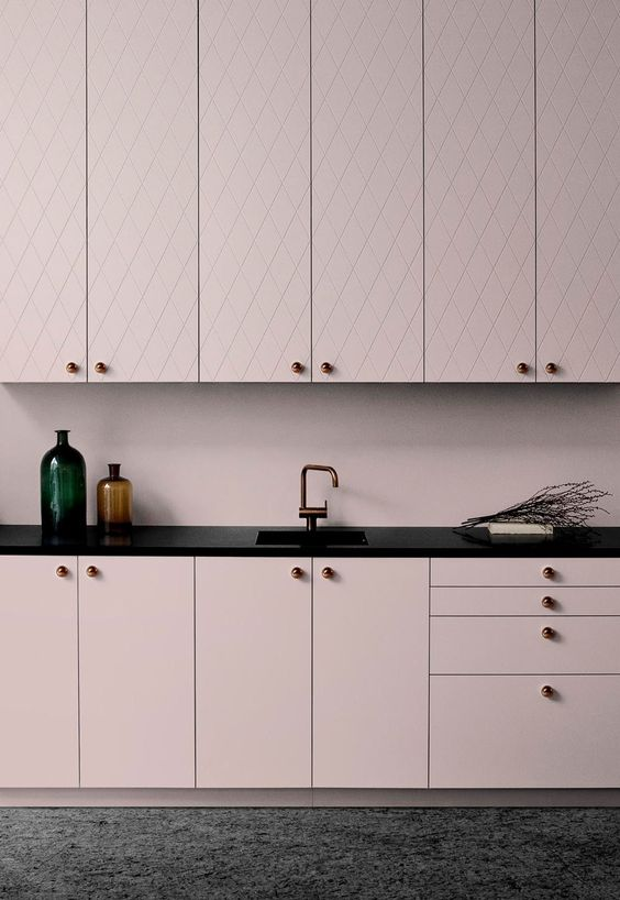 a chic pale pink kitchen with patterned and sleek cabinets, black countertops for a bold contrast