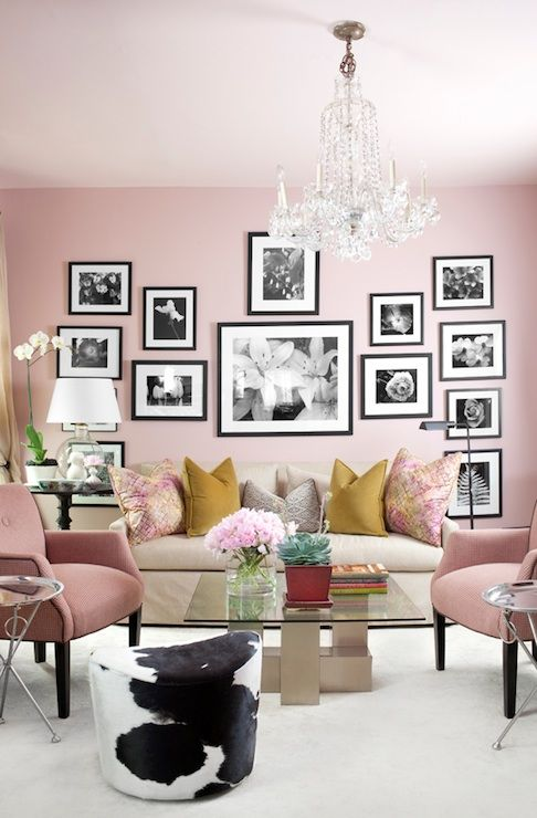 a chic pink living room with light pink chairs, a black and white gallery wall and colorful pillows