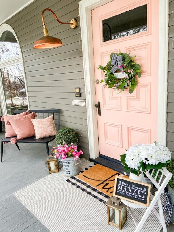 a chic summer porch with a black bench, pink pillows, a greenery wreath, lots of blooms and a chalkboard sign