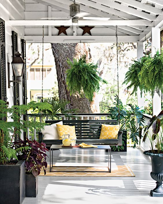 a chic summer porch with a black hanging bench, a black table and black planters with lots of greenery around