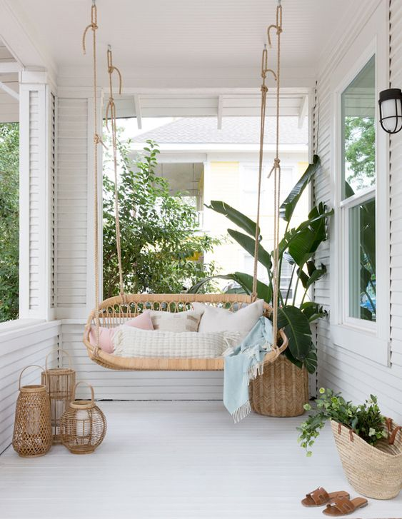 a chic summer porch with a hanging rattan bench, candle lanterns, a potted plant in a basket and some neutral textiles
