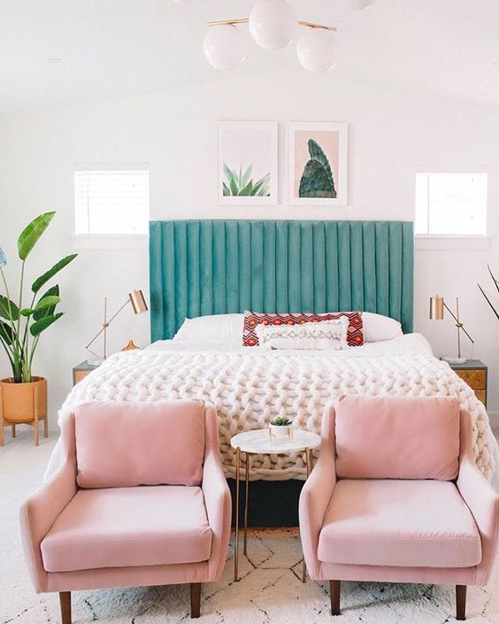 a chic tropical bedroom with a green upholstered bed, pink chairs, cacti and succulent artworks and tropical plants