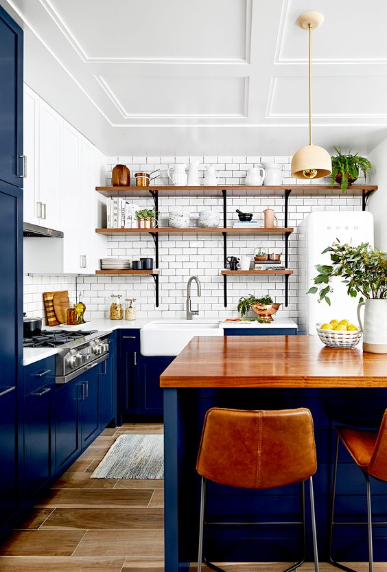 a classic blue kitchen with a white subway tile backsplash, white countertops and wooden open shelves