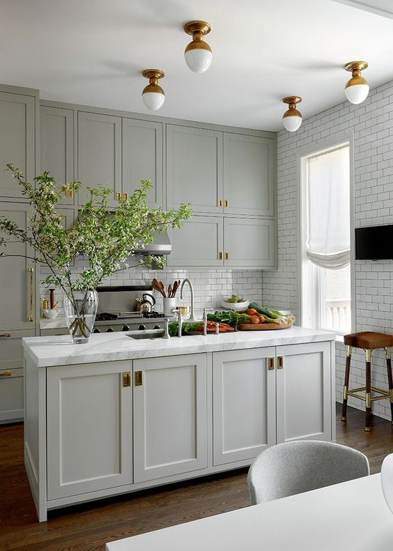 a classic grey kitchen with beautiful brass accents and flush mount lighting and white subway tiles on two walls