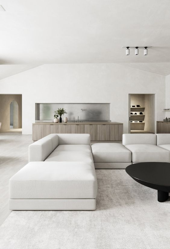 a clean minimal living room with a large neutral sofa, a black round table and nothing else