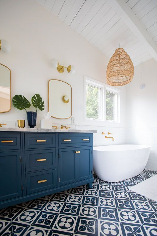 a coastal bathroom with white walls, navy and white mosaic tiles, navy vanities and touches of wicker
