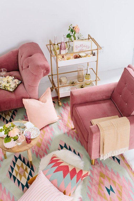 a colorful living room with pink furniture, blush pillows, a bright printed rug and touches of gold