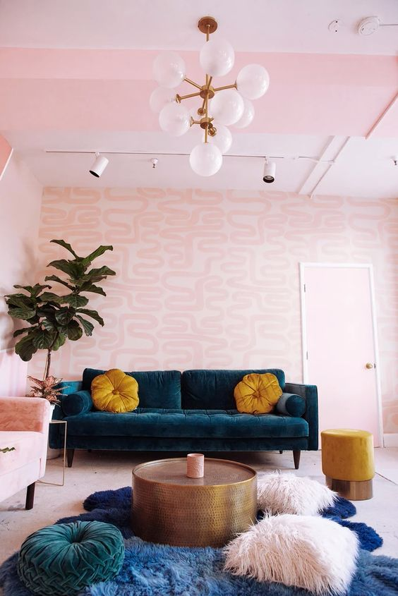 a colorful living room with printed pink walls, a striped pink ceiling, a pink chair and pillows plus touches of teal and mustard