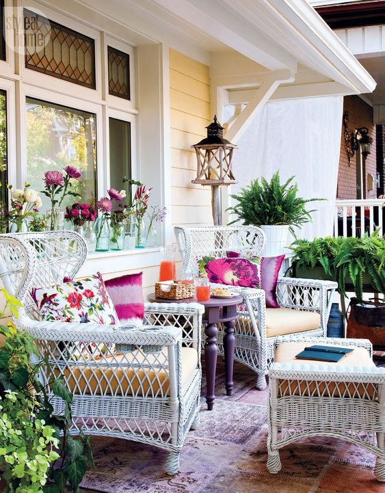 a colorful summer porhc with white wicker furniture, a purple table, lots of greenery, printed pillows and potted greenery