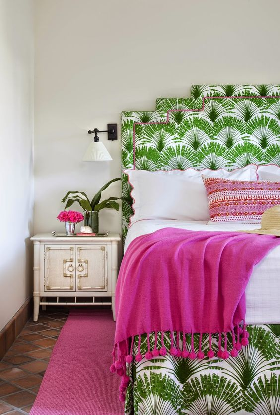 a colorful tropical bedroom with a printed bed, fuchsia textiles, a vintage nightstand and some blooms