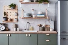 a contemporary dark green kitchen with a wallpaper wall, plywood shelving and a grey fridge is chic and stylish