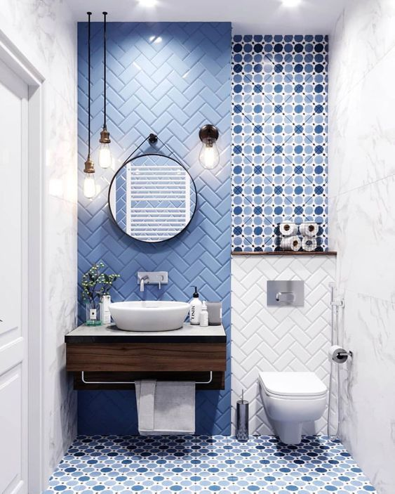 a contemporary powder room with a blue tile herringbone wall and polka dot tiles plus pendant lamps