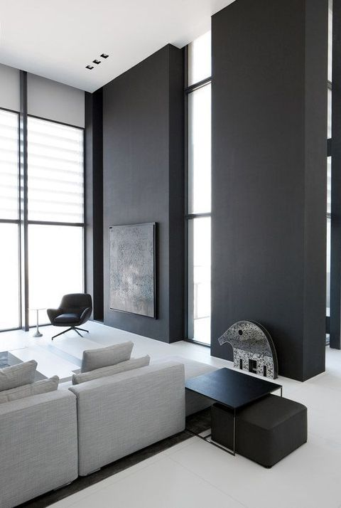 a contrasting minimalist space with black accent walls, several windows, a grey sectional and dark tables