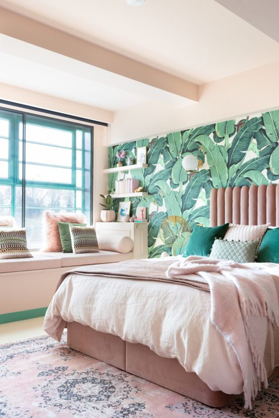 a cool tropical bedroom with a banan leaf wall, a pink bed, green and pink pillows plus white furniture