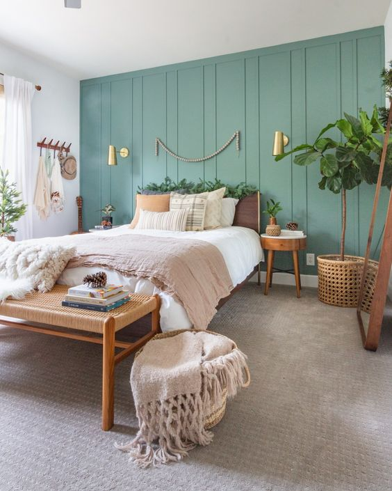 a cozy boho bedroom with a light grene accent wall, some cozy wood and rattan furniture and potted greenery