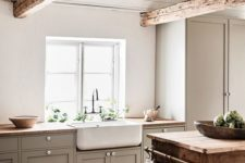 a cozy farmhouse neutral kitchen with grey cbainets, wooden countertops and beams, a wooden cart kitchen island
