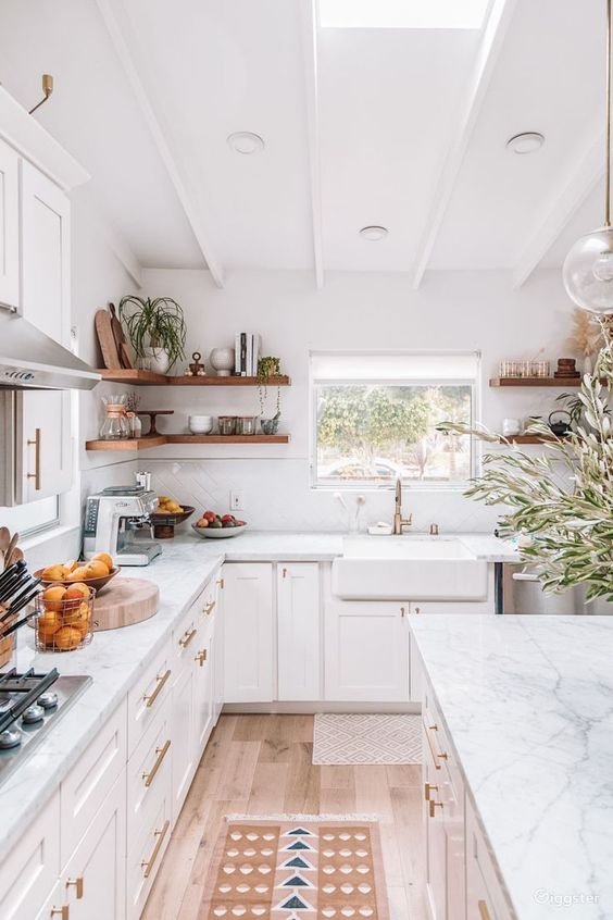 a cozy neutral kitchen with skylights, white marble countertops, built-in shelves and touches of gold for some glam