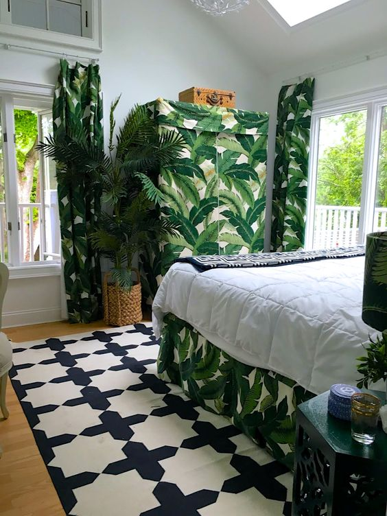 a crazy tropical bedroom done in a monochromatic color scheme and spruced up with tropical prints, woven touches and skylights